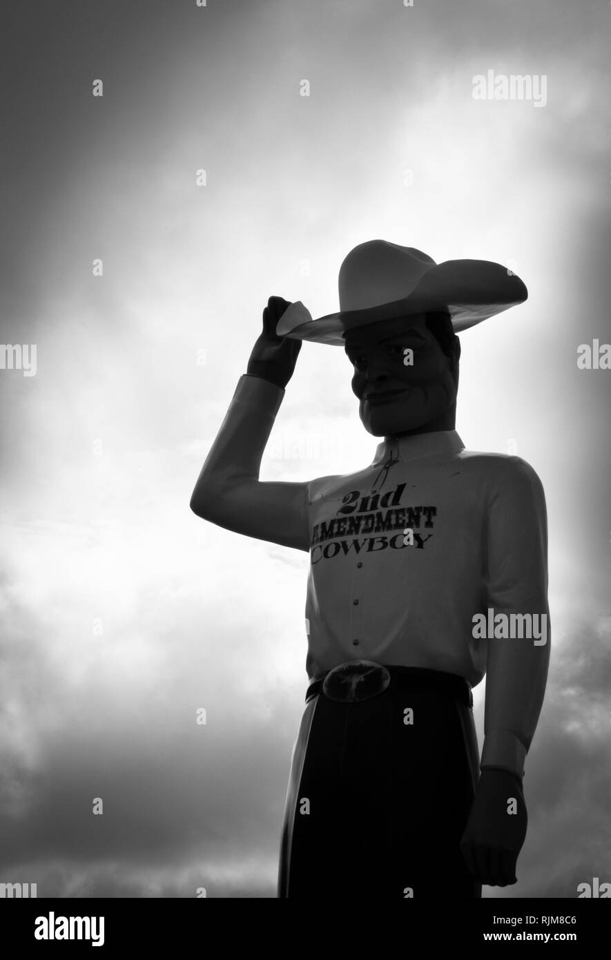 A giant sculpture of a cowboy wearing a 'Second Amendment Cowboy' shirt, tipping his 10 gallon stetson hat as Roadside Attraction near Amarillo, TX - Stock Image