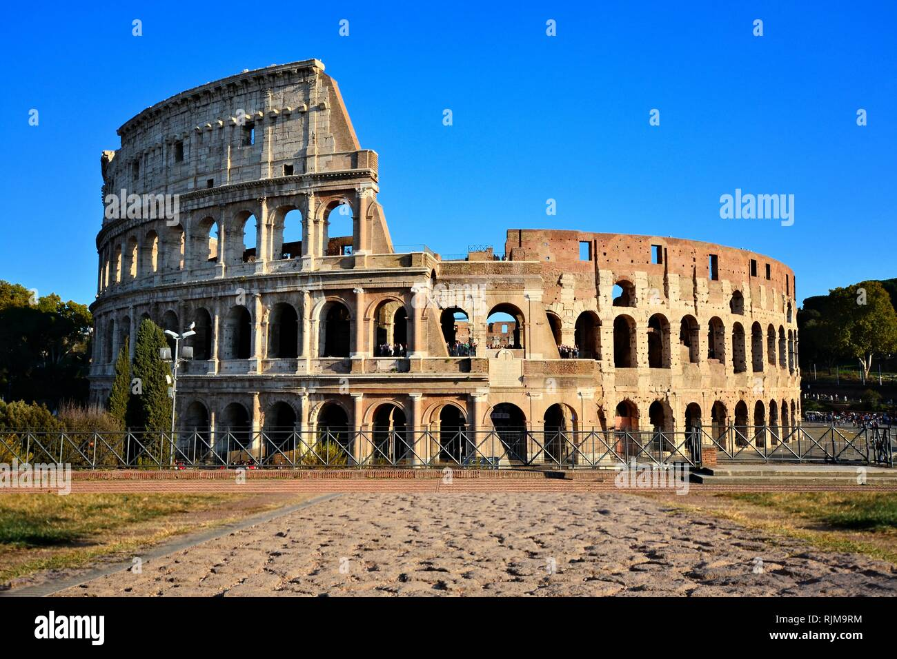 Rome, Italy, the Coliseum. View from Forum with ancient stone road. Stock Photo