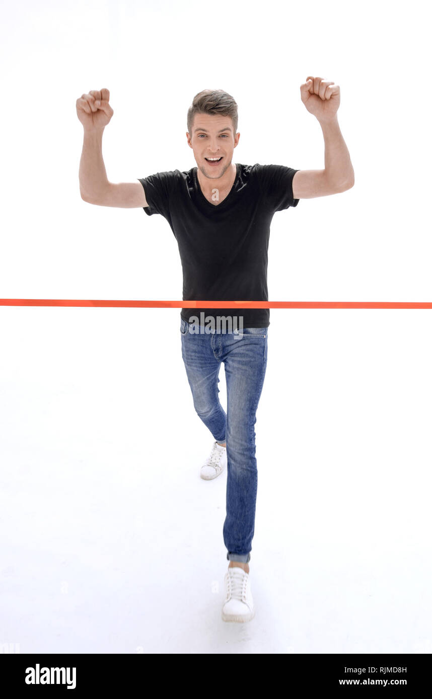 triumphant man in front of the finish tape - Stock Image