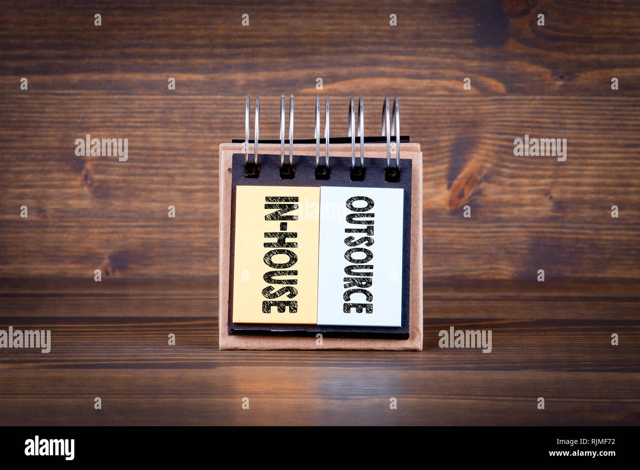 Outsource in-house concept. Notebook on dark wood background - Stock Image