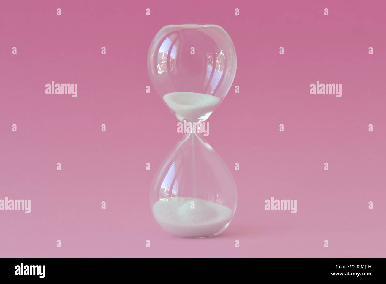 Hourglass on pink background - Concept of health, fertility and biological clock in women - Stock Image