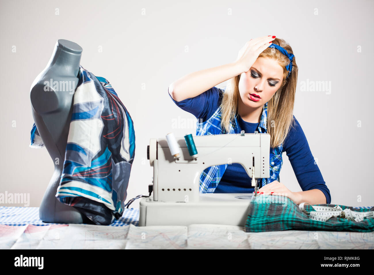 Woman sews and realizes that she made a mistake Stock Photo
