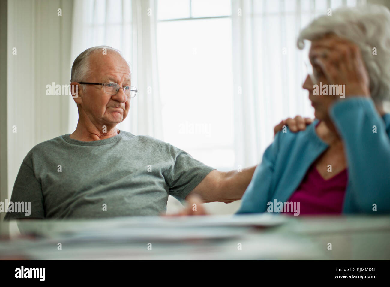 Anxious elderly couple are worried about a bill that they have received. - Stock Image