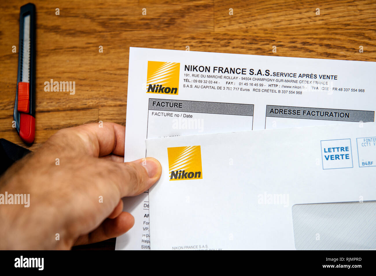 PARIS, FRANCE - Aug 8, 2018:  Man holding on office table a letter and invoice from Nikon Corporation for the camera equipment  - Stock Image
