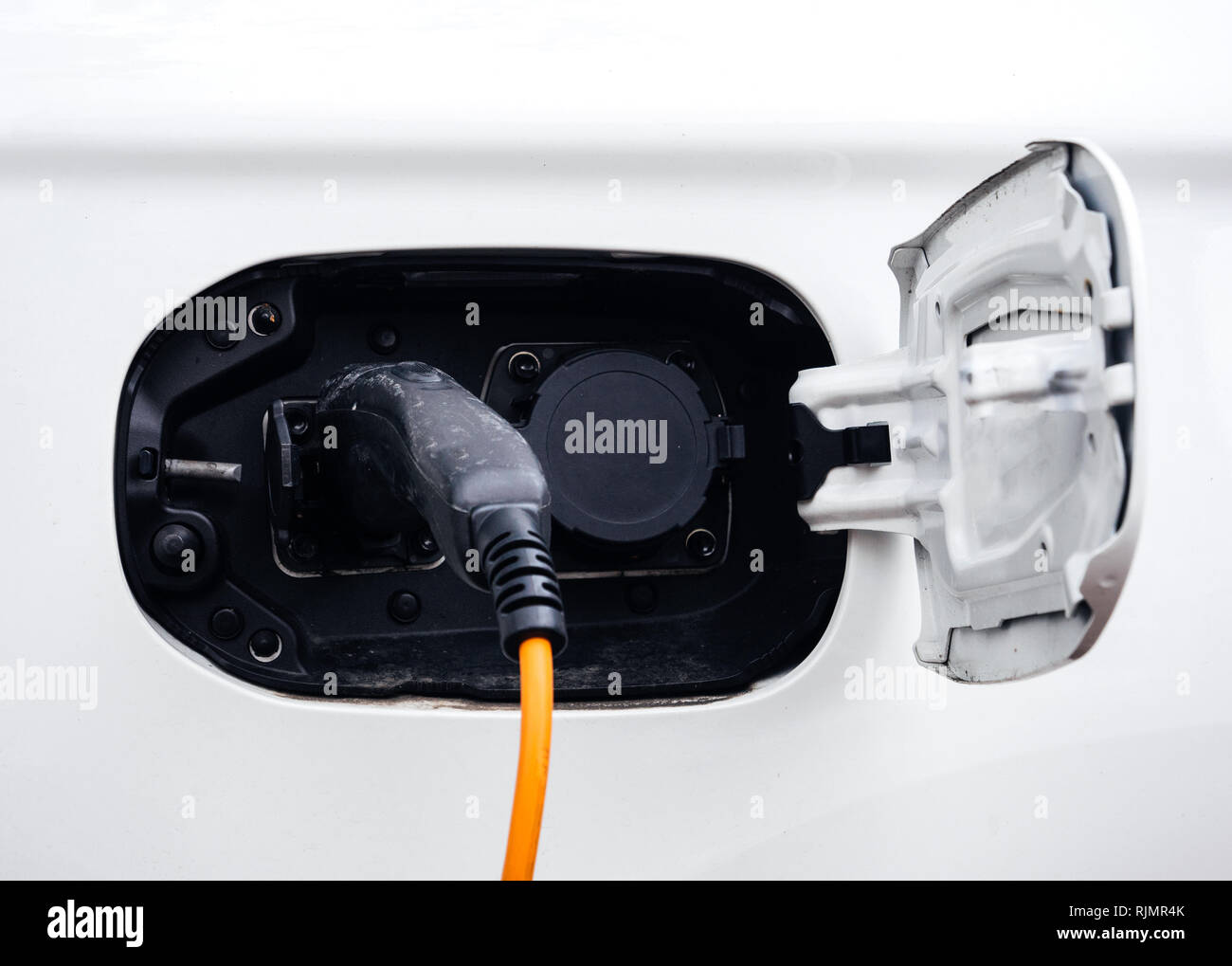 Yellow and black cable of electric car charger being plugged in at the parking - modern ecological clean environment car - Stock Image