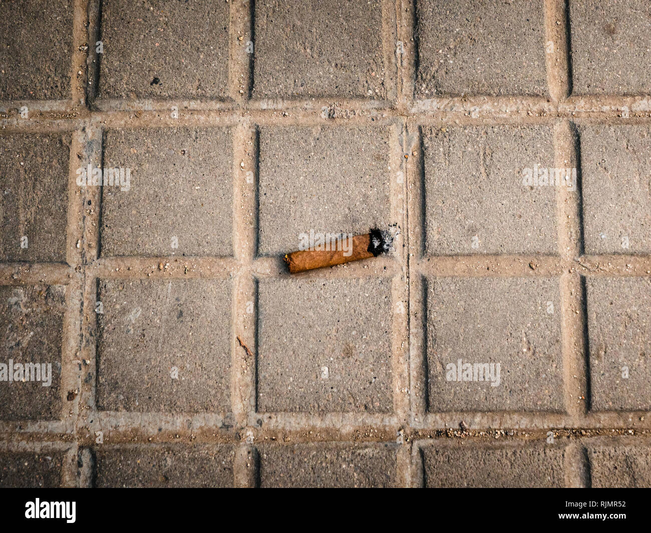 Above view of cuban cigar stub on gray concrete pavement - Stock Image