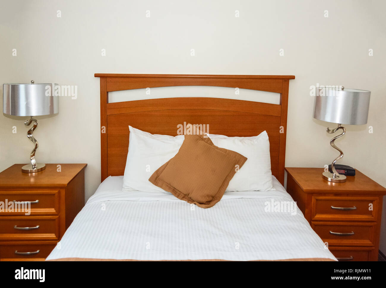 Twin bed in the bedroom with the lamp on bedside tables - Stock Image