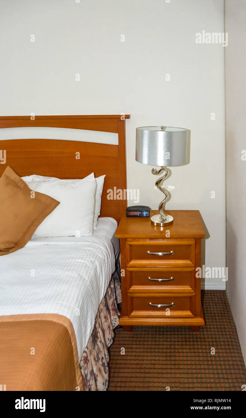 Silver lamp and radio watch on wooden bedside table beside the bed - Stock Image