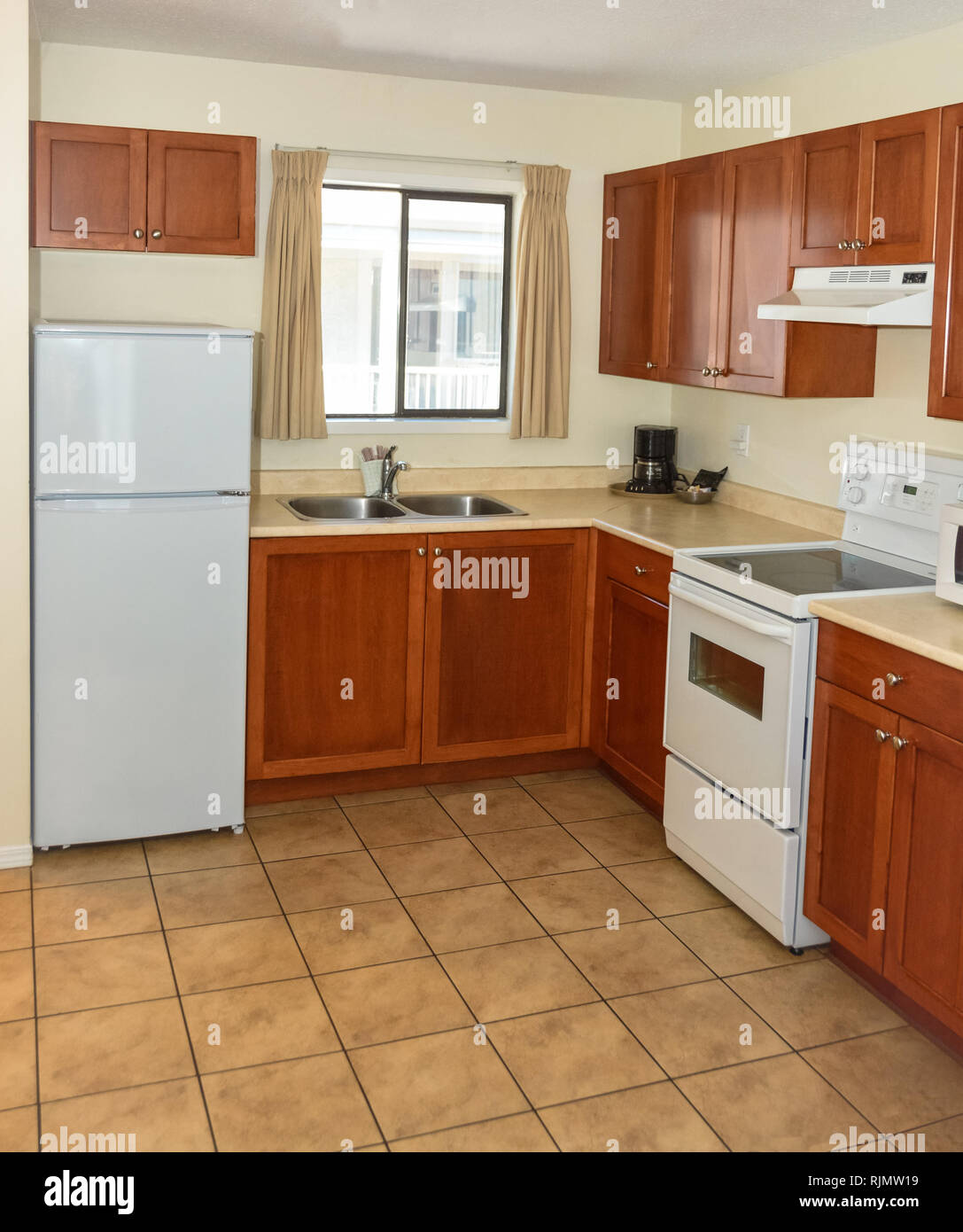 Small Kitchen With Wooden Cabinets Fridge And Electric