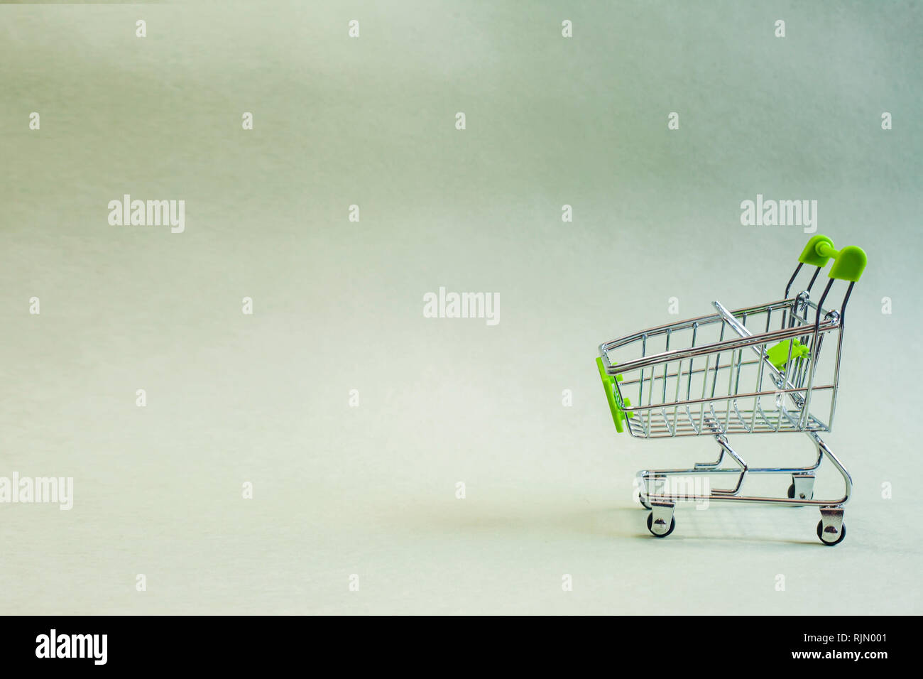 A green mini shopping cart on bright green paper background, blank for copy space. - Stock Image