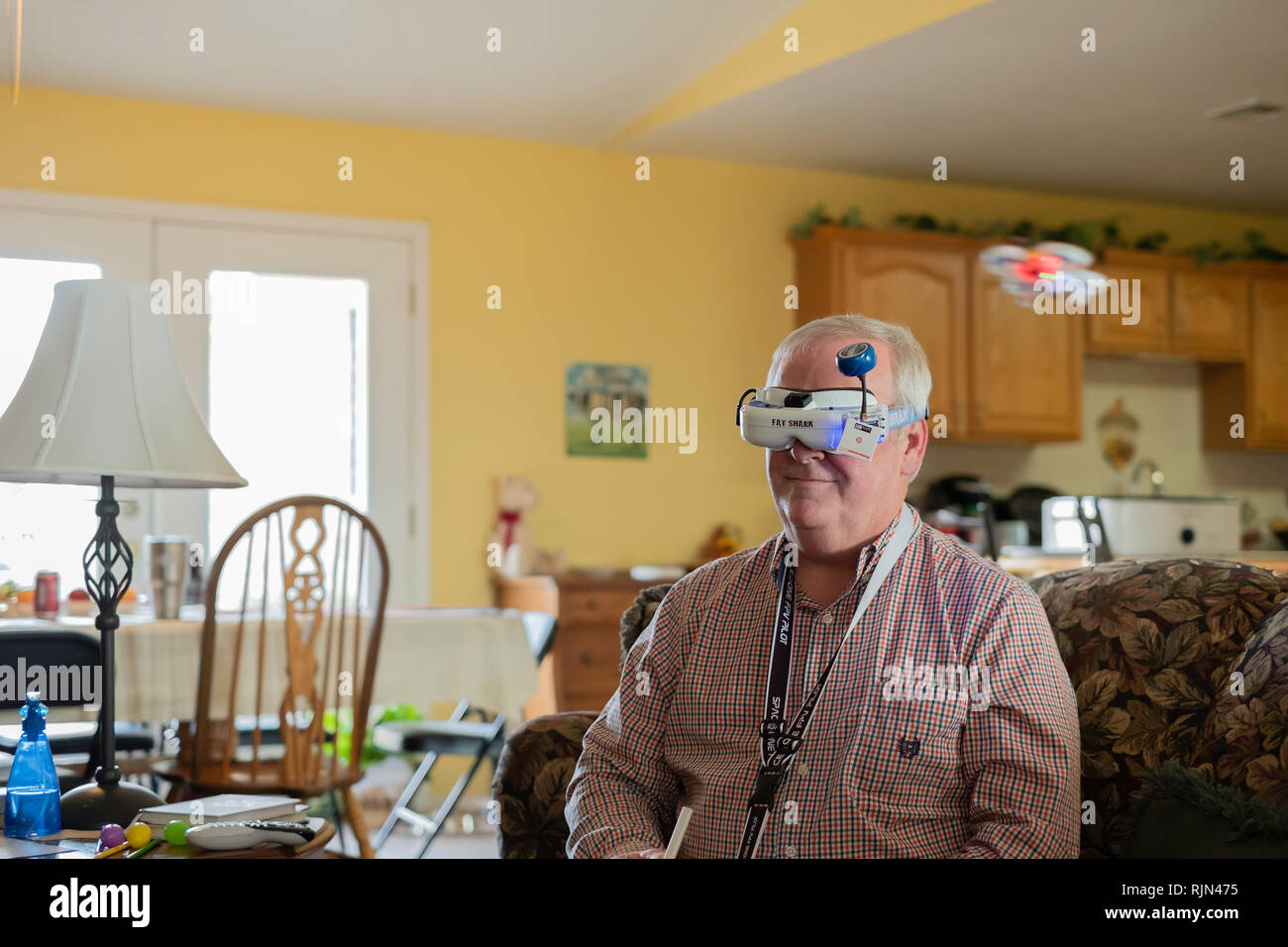 Fat Shark drone goggles worn by a 55 year old Caucasian man to visualize his small EACHINE E10 mini UFO quadcopter drone flying inside a home. USA. - Stock Image