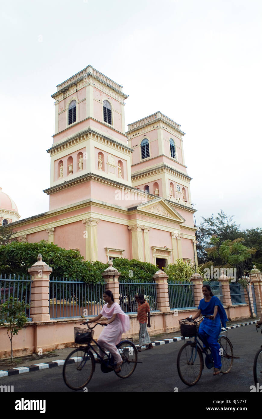 Cyclists pass a French-era church in Pondicherry - otherwise known as Puducherry in Tamil Nadu, India. The tiny French colony in India's remote southe - Stock Image