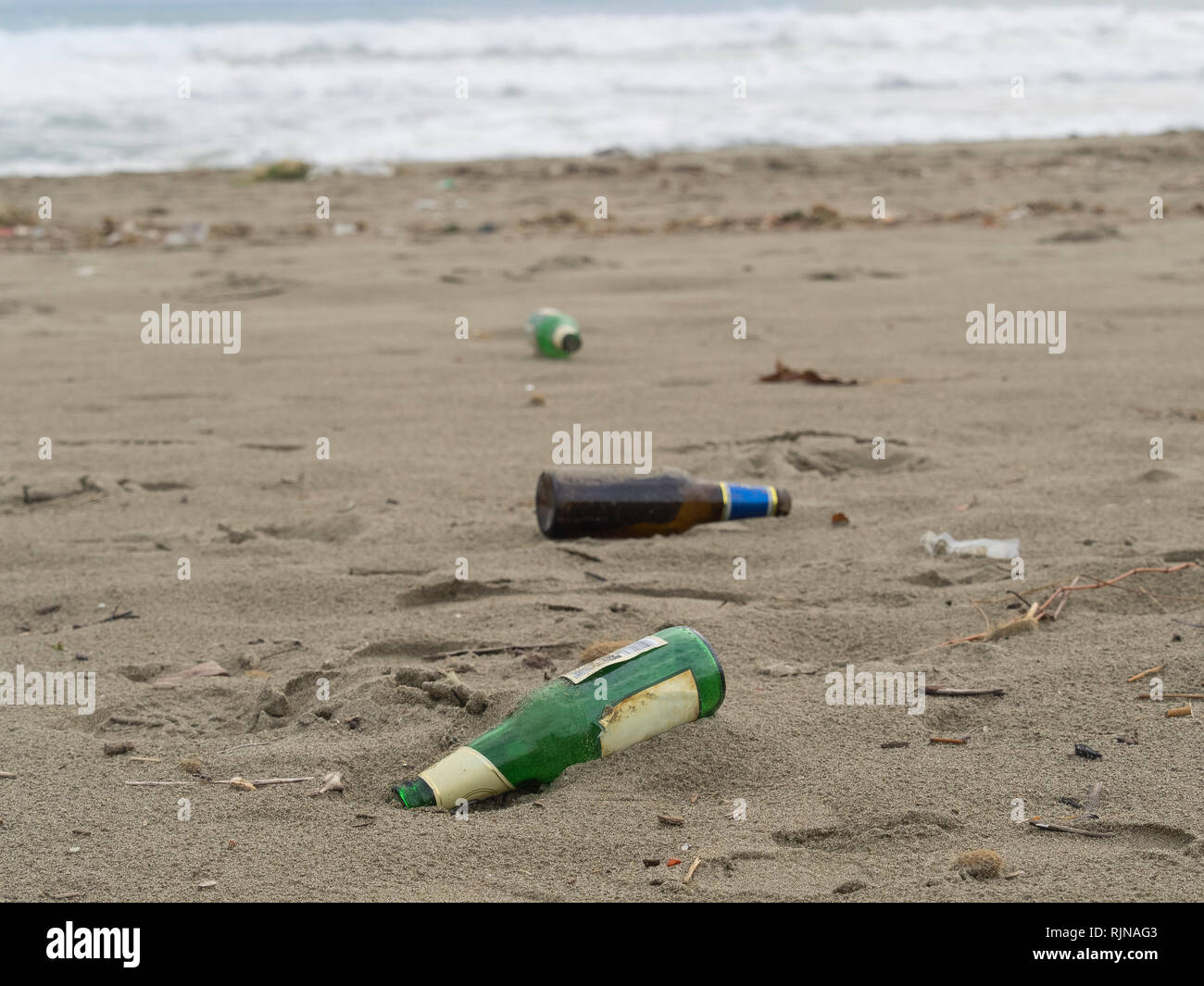 trash on the beach:  glass beer bottles abandoned on the sand - Stock Image