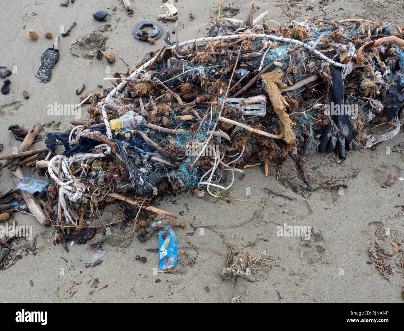 fishing net arrived on the beach full of plastic waste. Symbol fo ocean pollution. Danger fo marine life - Stock Image