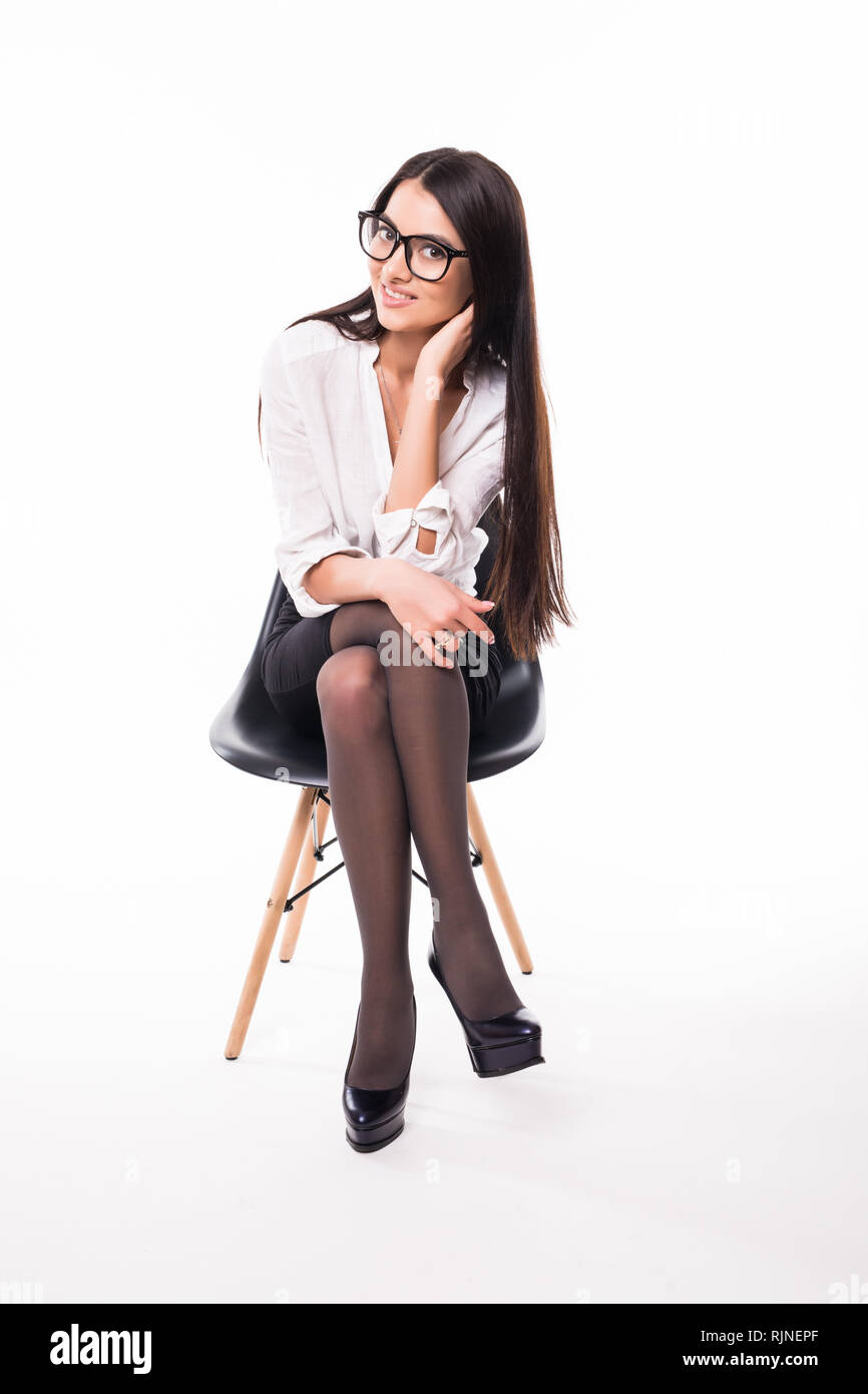 46cb89b08f14 Businesswoman sitting on a chair isolated on white background - Stock Image