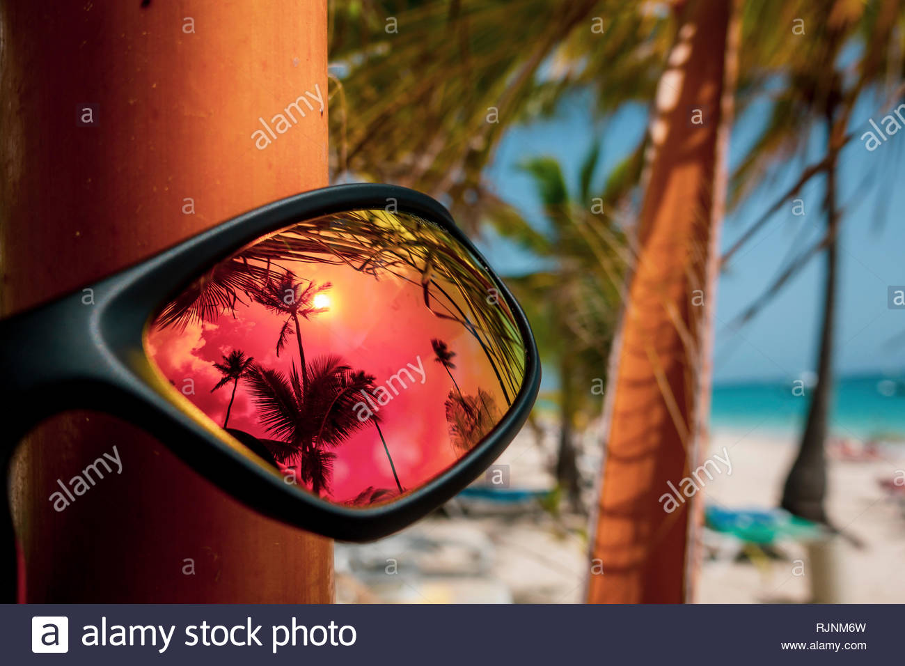 Orange sunglasses with palm trees at the beach of Punta Cana in the Dominican Republic - Stock Image