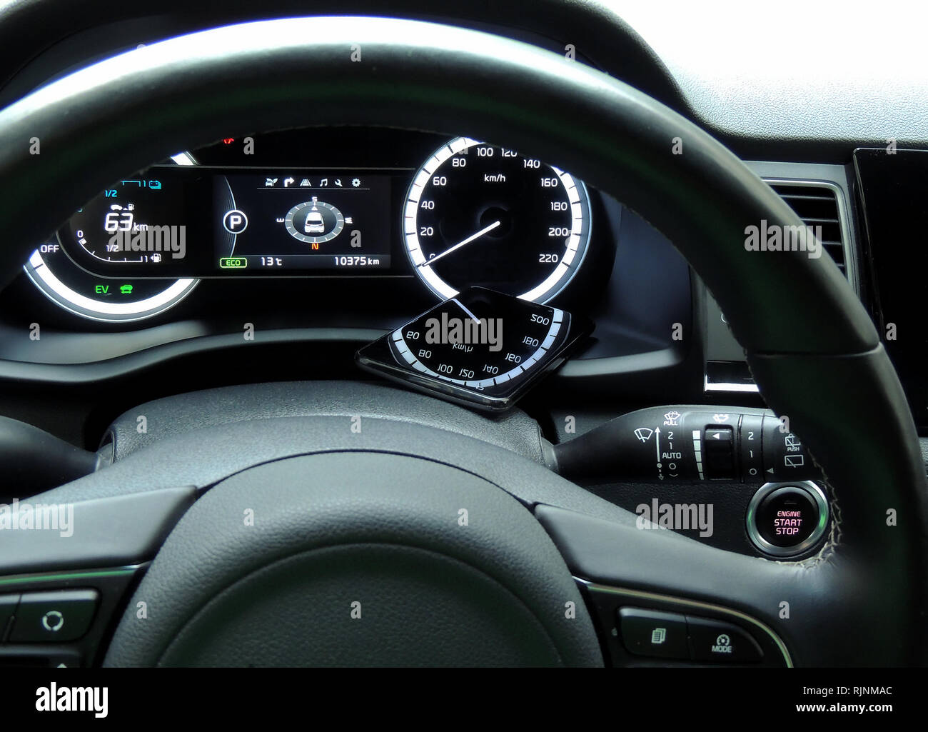 Speedometer digits reflected on the glossy surface of mobile phone on the car dashboard - Stock Image