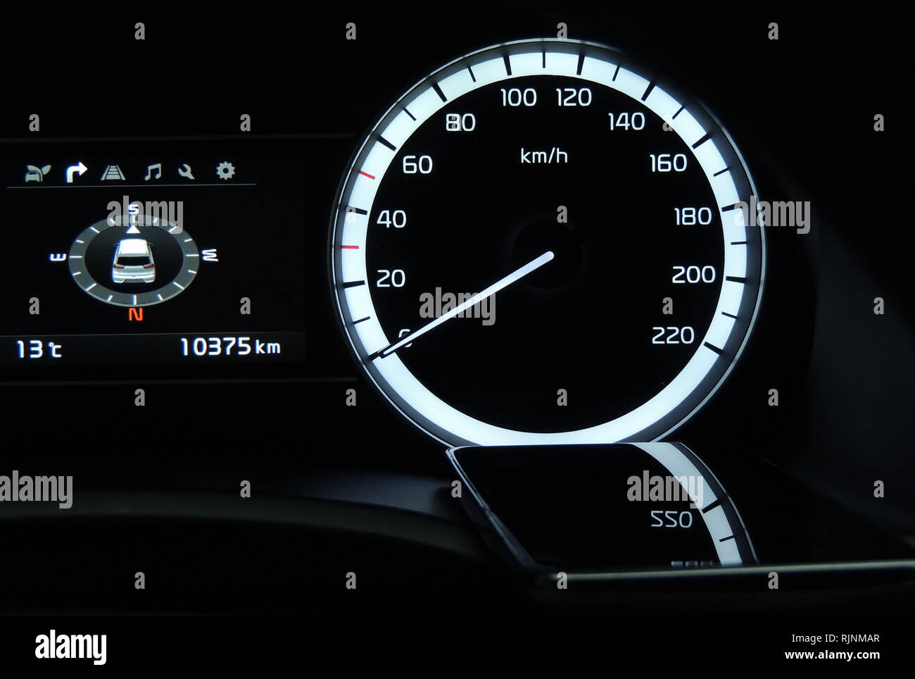 Mobile phone indicate reflection of car speedometer and digital navigation close up - Stock Image