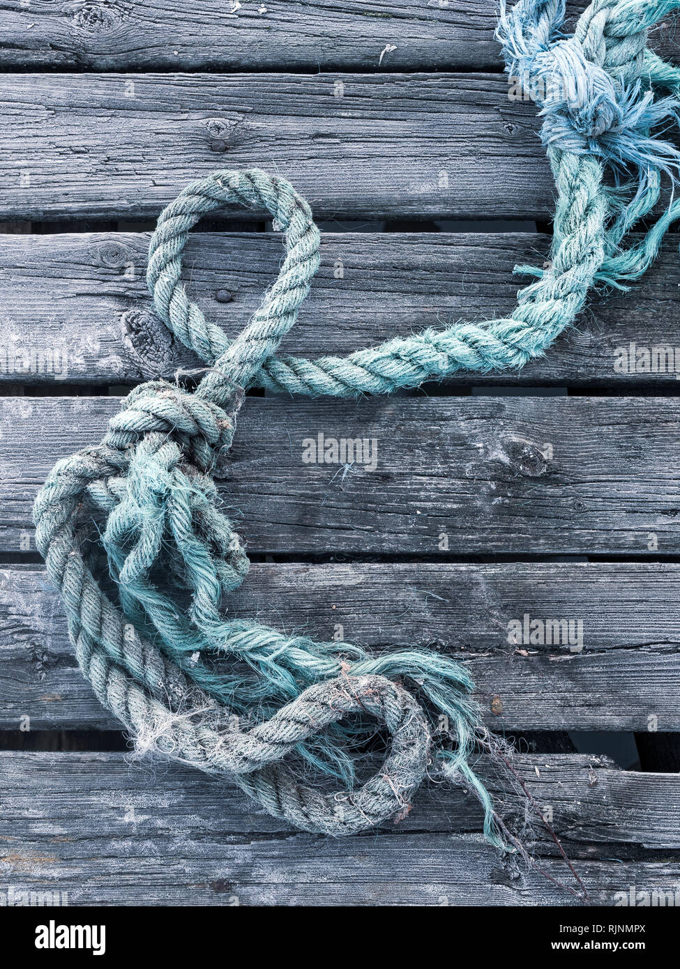 Blue rope on top of weathered wooden planks, full frame, close up - Stock Image
