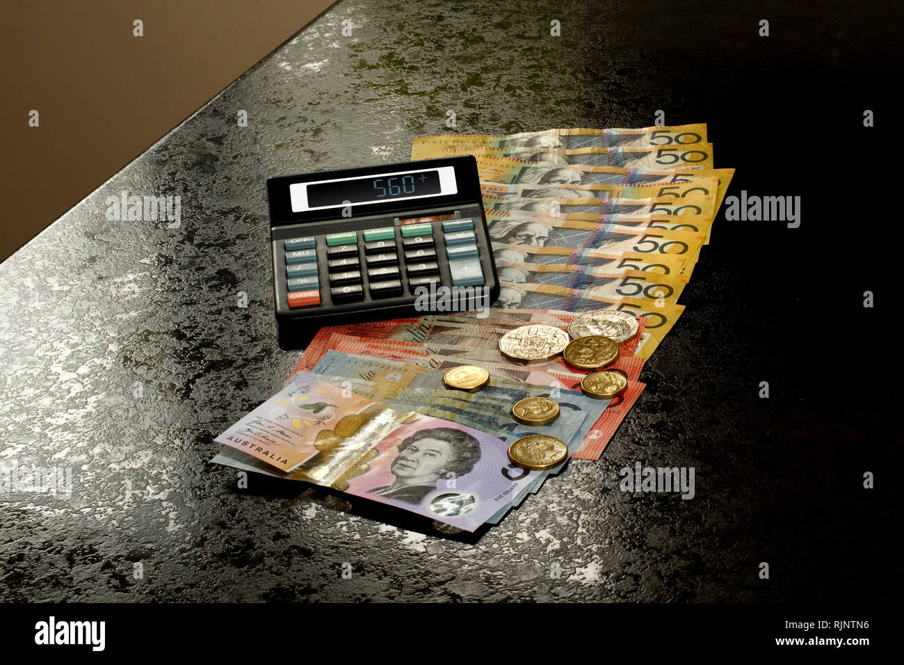 Australian Dollars and coins on a kitchen counter with calculator Stock Photo