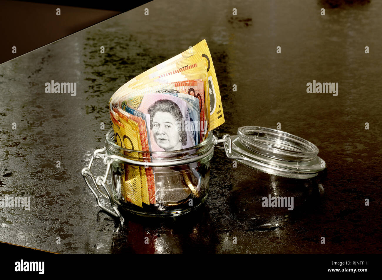 Australian Dollars in a glass jar on a kitchen counter Stock Photo