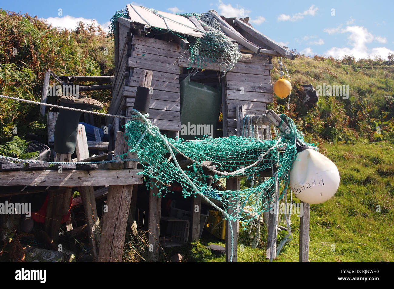 A ramshackle hut made up on a lonely beach near Polbain, Scotland,made out of old timbers, netting, bouys and hung with ropes and washed up debris - Stock Image