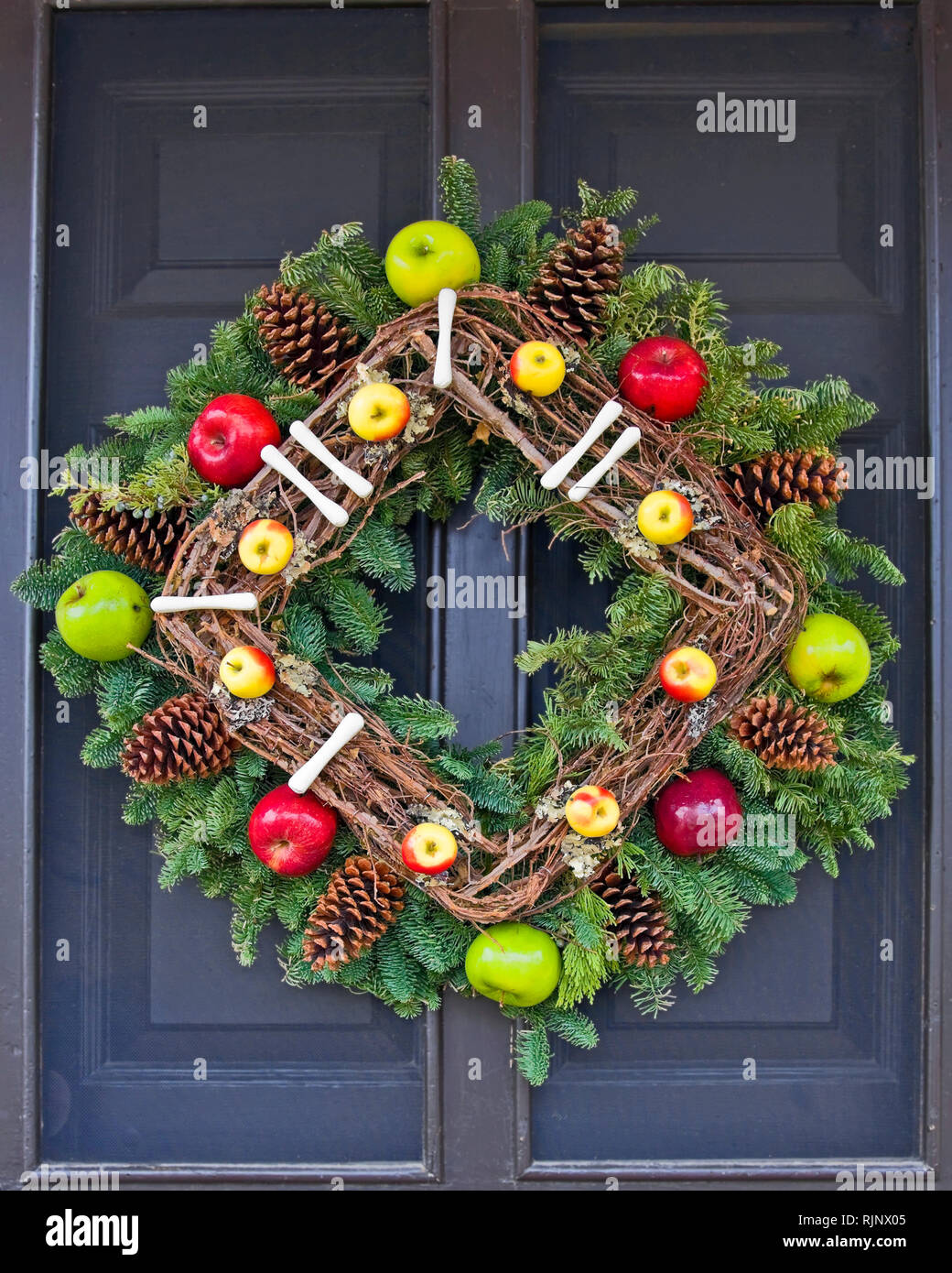 Christmas decoration; square wreath; apples; pine cones; evergreens; grapevines; hung diagonally; black door, holiday; festive; unique; colorful; vert - Stock Image