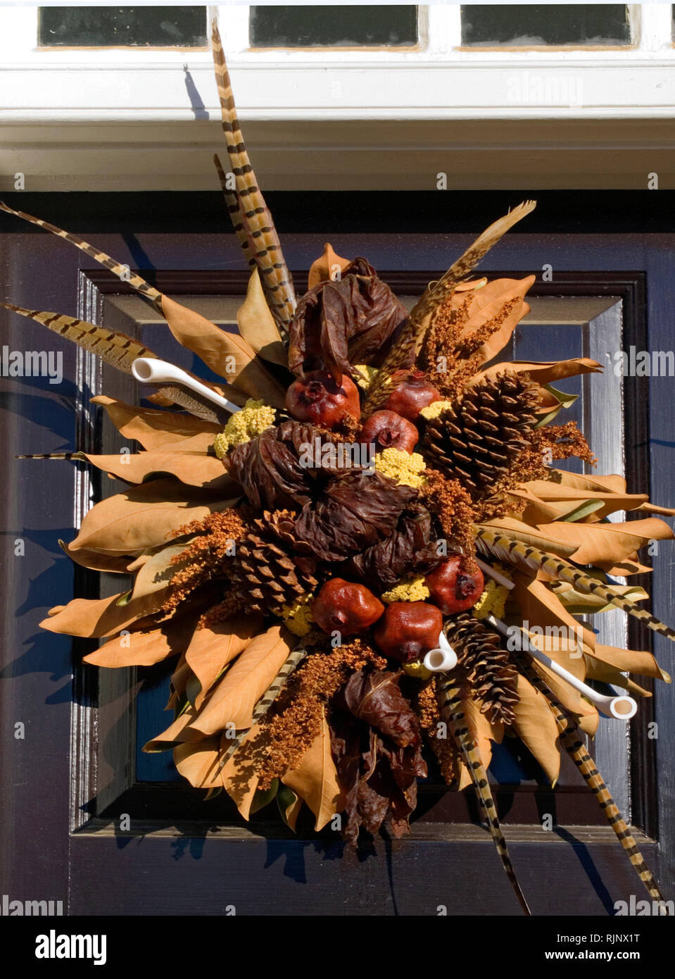 wreath, black door; natural materials; brown tones; dried leaves, pine cones, red apples, feathers, white pipes, autumn, seasonal, decoration; vertica - Stock Image