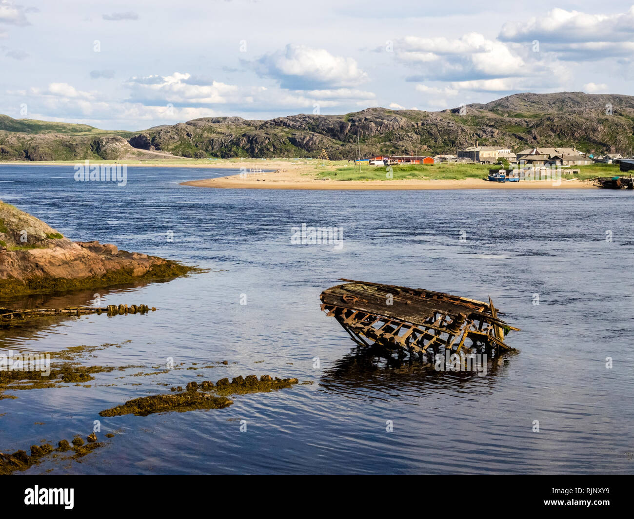 Sunken old wooden fishing boat in Teriberka, Murmansk Oblast, Russia - Stock Image