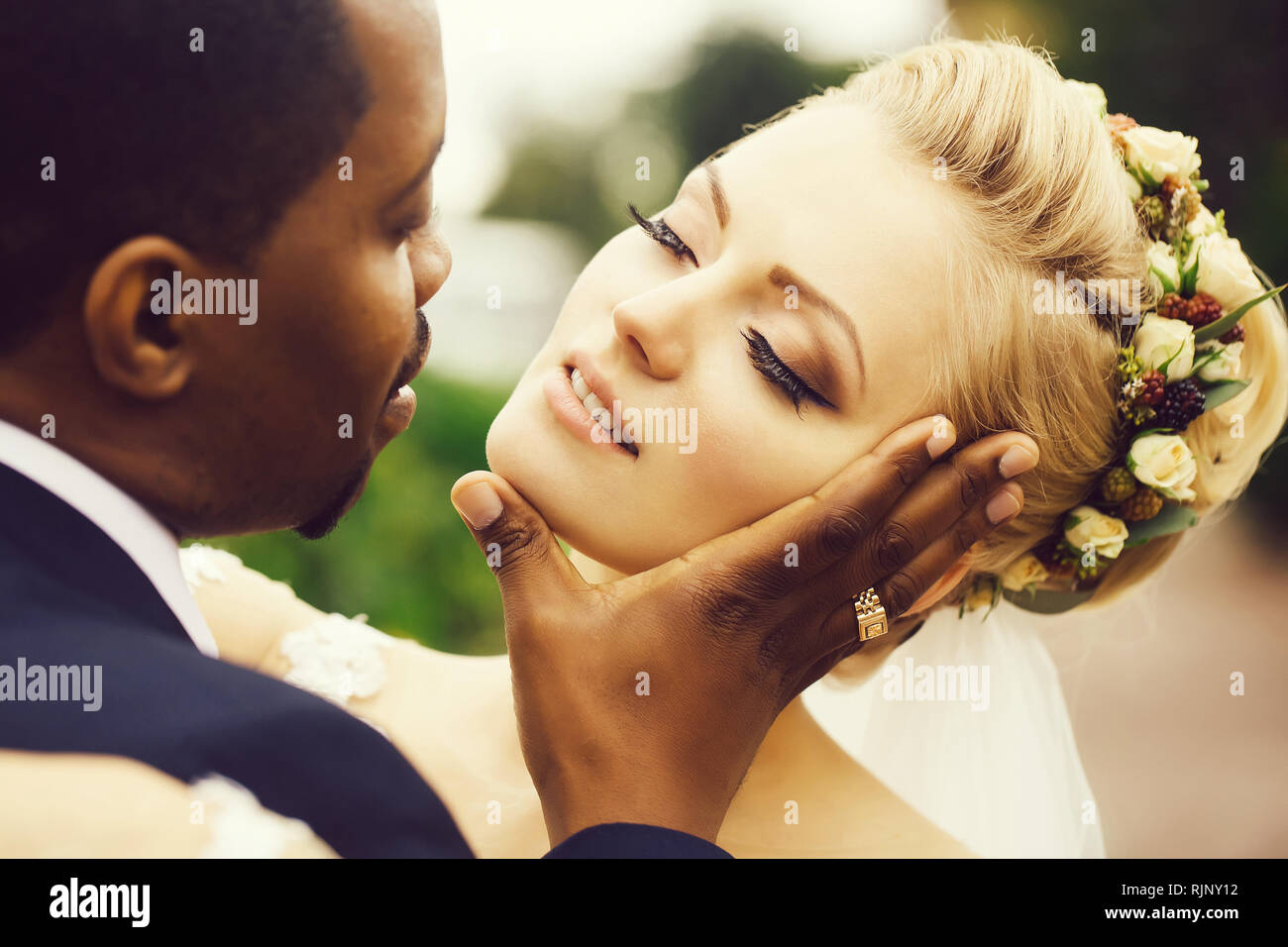 Groom touches face of bride - Stock Image