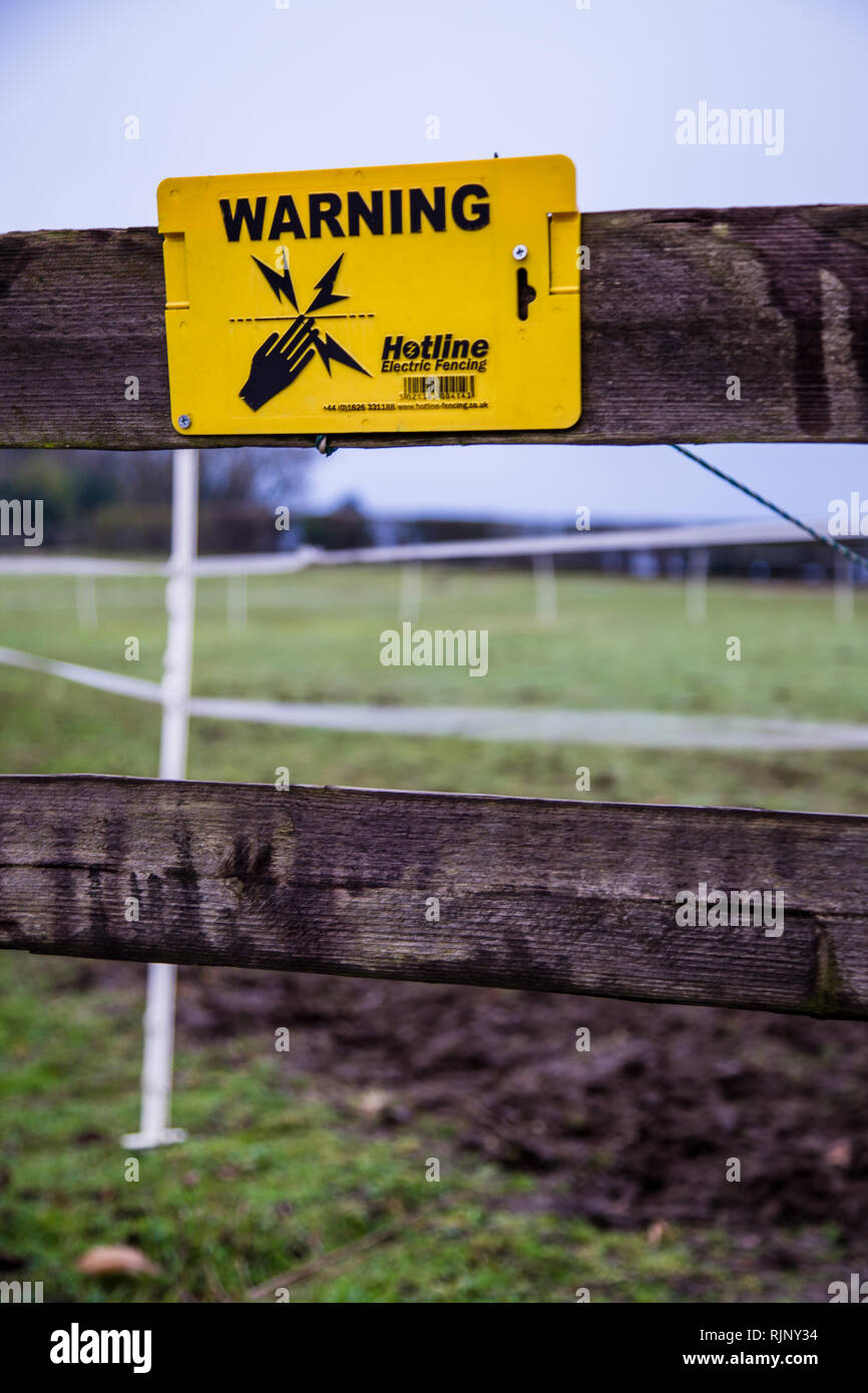 Electric fence warning sign, warning of the danger of electrocution or shock if touching the fence - Stock Image