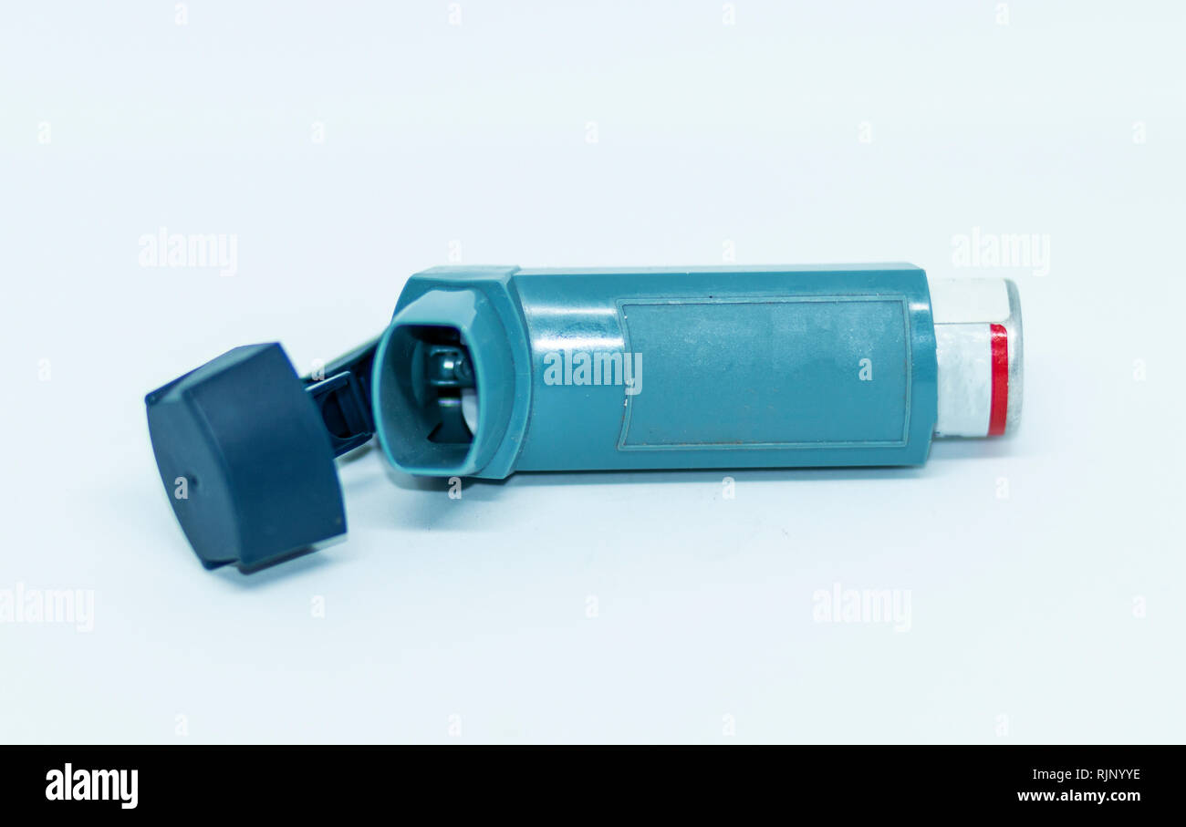 One blue inhaler with its cap open lying on its side in front of a white background. - Stock Image