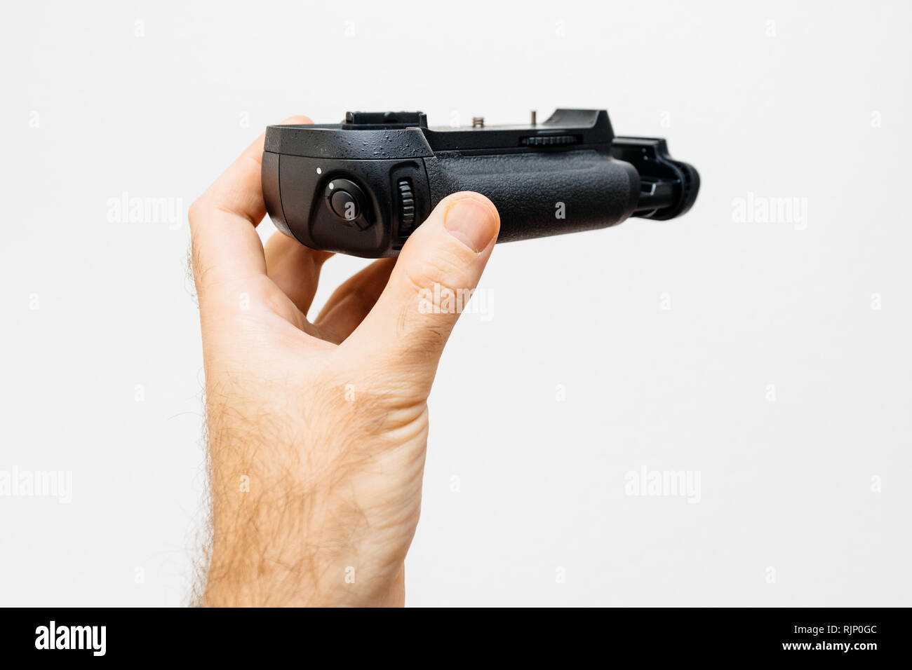 Photographer hand holding against white background a new modern battery camera grip for his new camera full frame DSLR and mirrorless camera - Stock Image