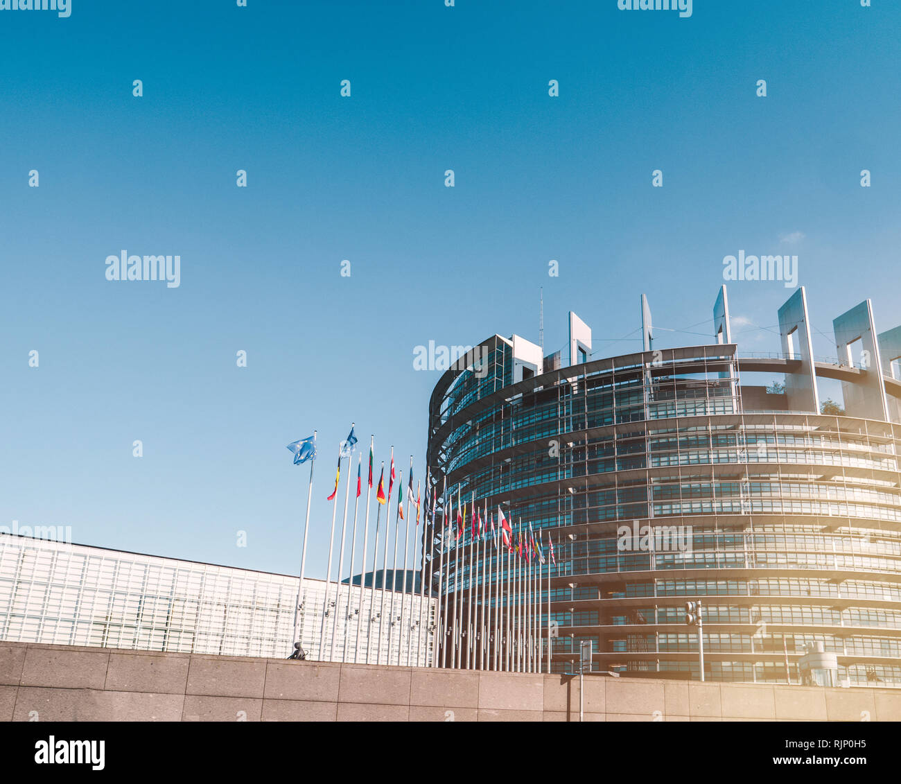 STRASBOURG, FRANCE - SEP 3, 2017: Exterior shot of contemporary building of European parliament with flags waving under blue sky, France - large copy space on the blue sky - Stock Image