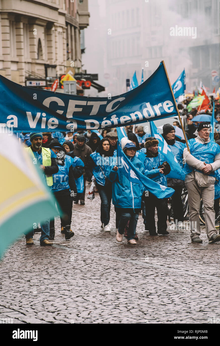 STRASBOURG, FRANCE - MAR 22, 2018: Group of people in blue carrying flags and performing organized protest meeting walking on street, France - Stock Image