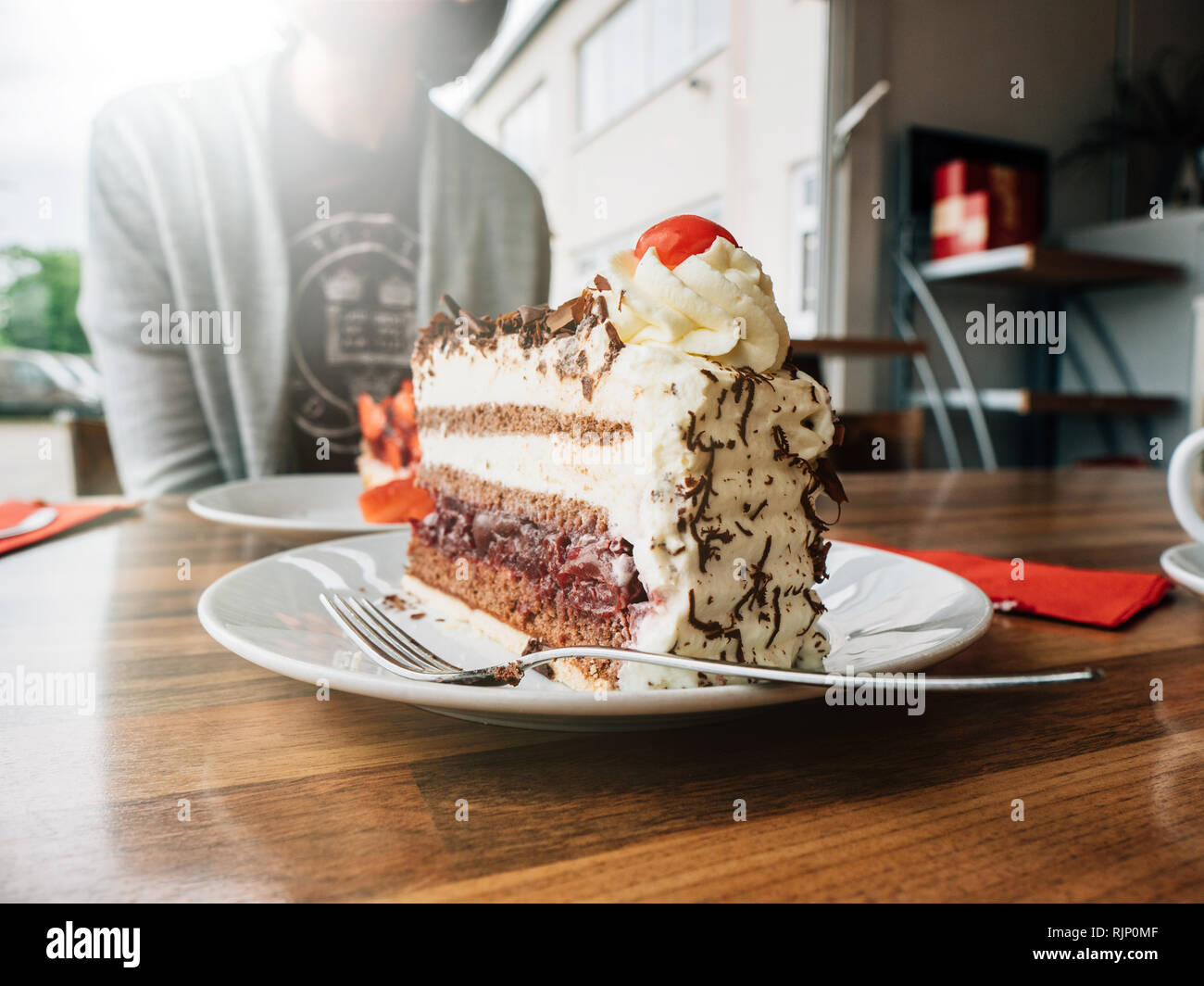 German woman having delicious strawberry Black Forest dessert with cup of coffee in cafeteria - Stock Image