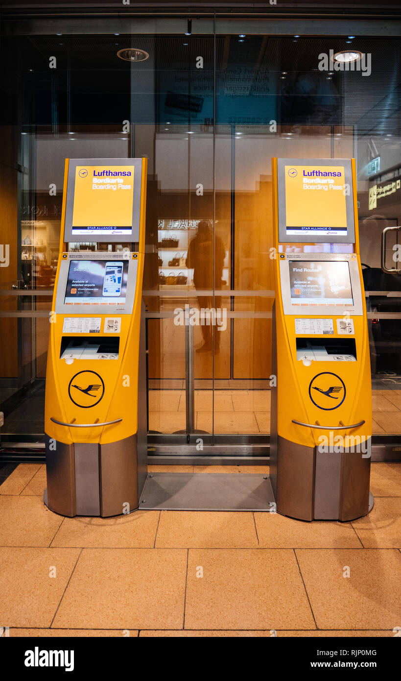 HAMBURG, GERMANY - MAR 22, 2018: Yellow electronic terminals for check-in placed in hall of airport from Lufthansa boarding pass - Stock Image
