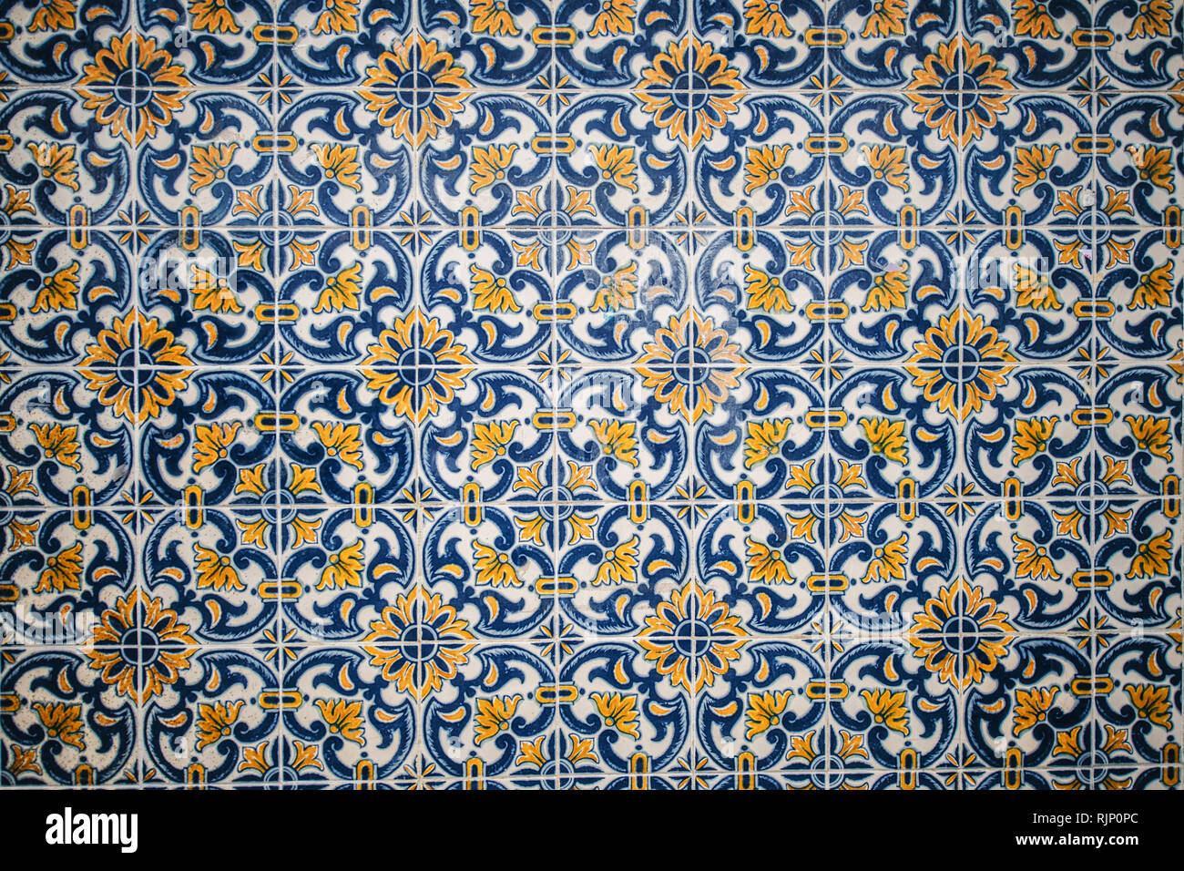 Background of wall in ornamental azulejos tiles in beautiful blue and yellow colored design - Stock Image