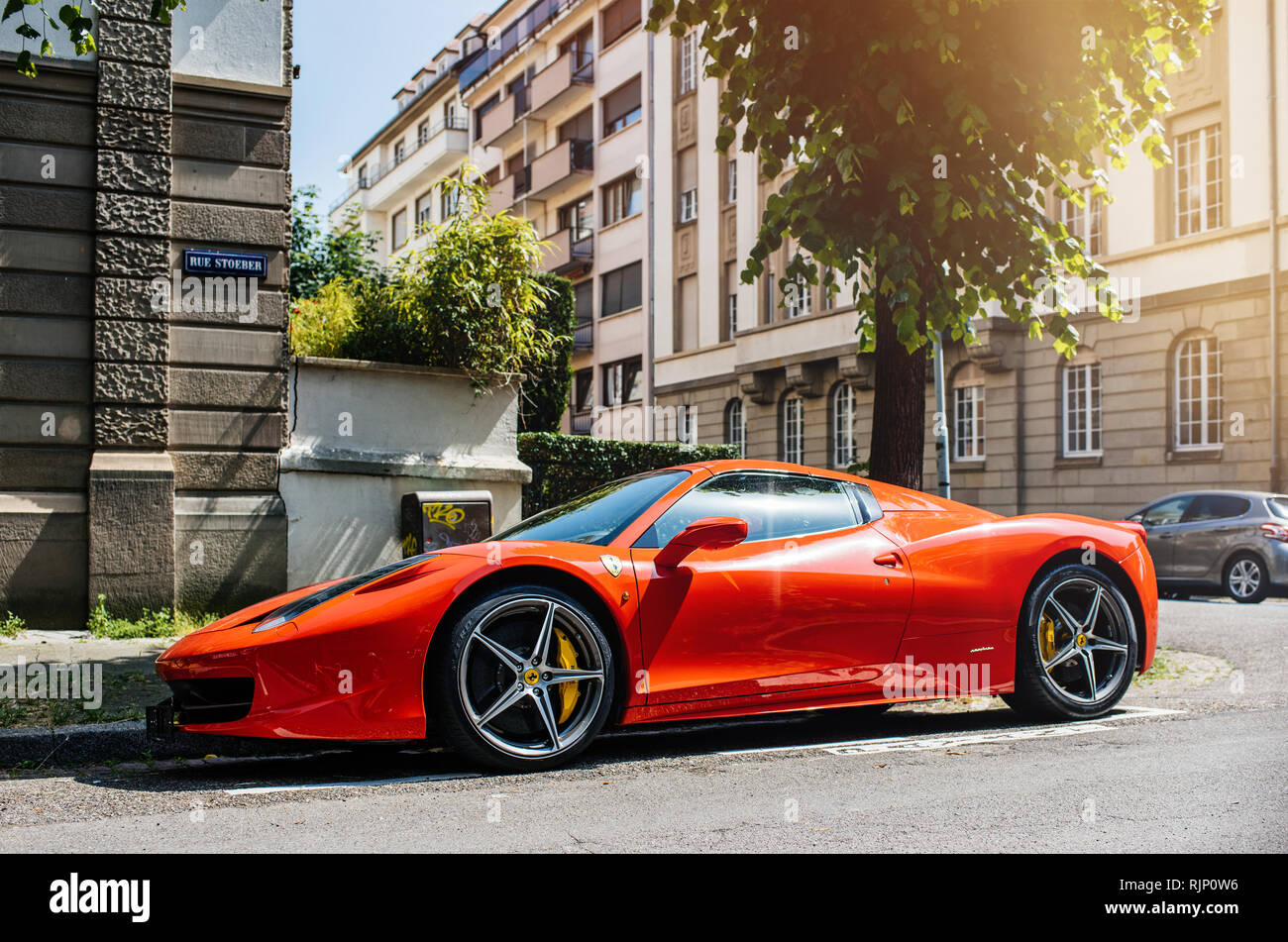 STRASBOURG, FRANCE - MAY 28, 2018: City parking with expensive luxury Ferrari car red color parked on street in sunlight - Stock Image