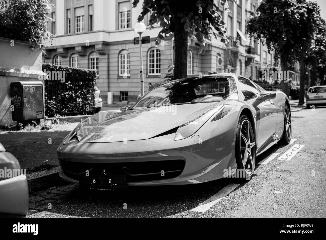 STRASBOURG, FRANCE - MAY 28, 2018: City parking with expensive luxury Ferrari car parked on street in sunlight - black and white - Stock Image