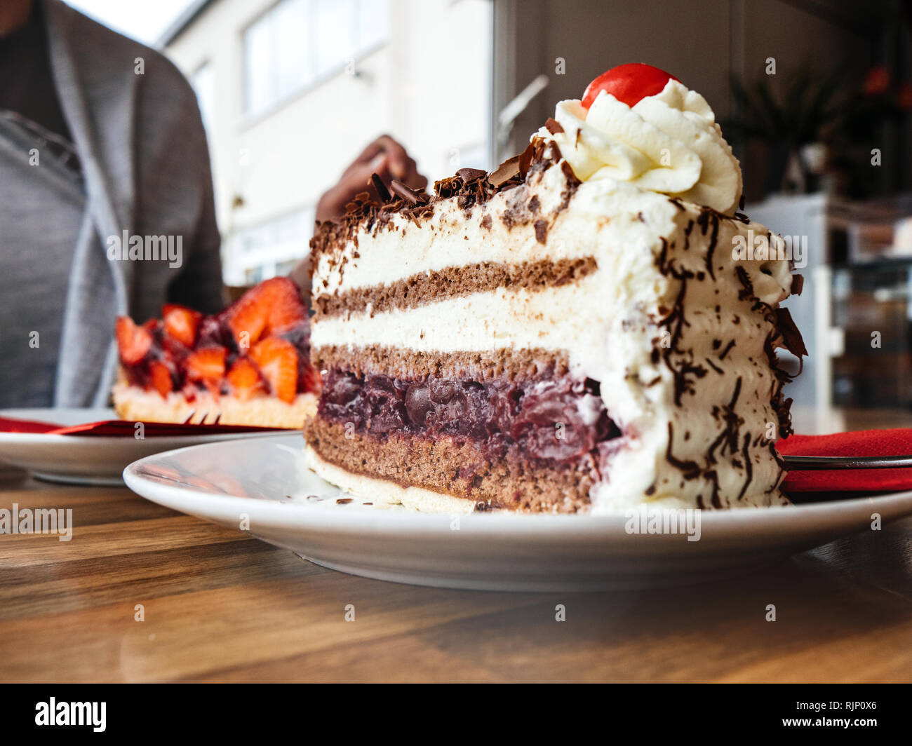 German woman having delicious strawberry dessert with cup of coffee in cafeteria Black Forest cake - Stock Image