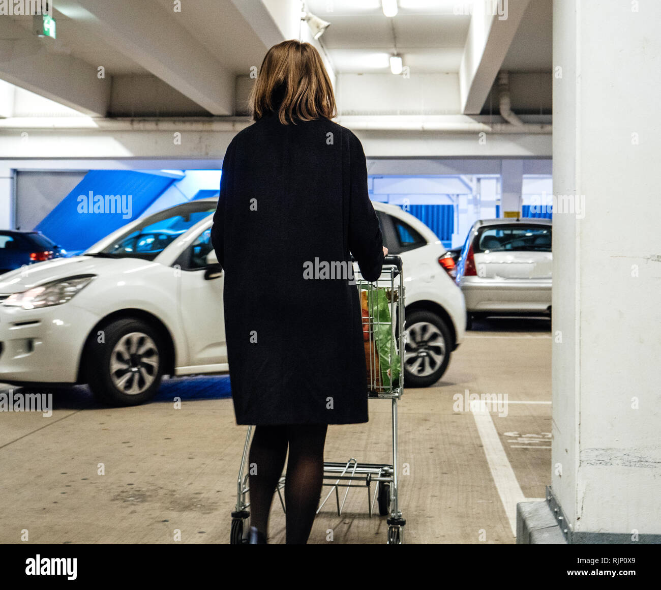 Rear view of woman pushing shopping trolley to car parking with bags with groceries parking lot - Stock Image