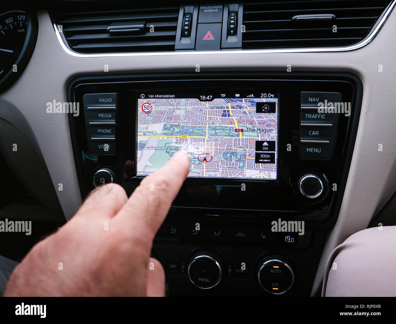 THE HAGUE, NETHERLANDS - AUG 19, 2018: Crop shot of male finger pointing at GPS tablet inside of car while navigating in city of Hague, Netherlands on Van Alkemadelaan street - Stock Image