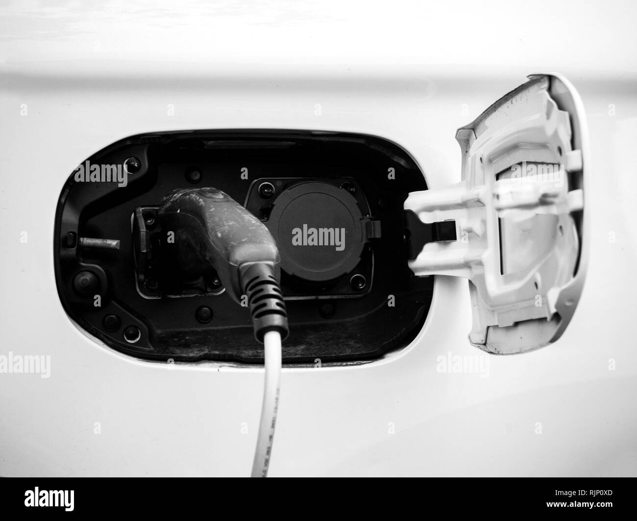 Energy power cable of electric car charger being plugged in at the modern refueling center station - Stock Image