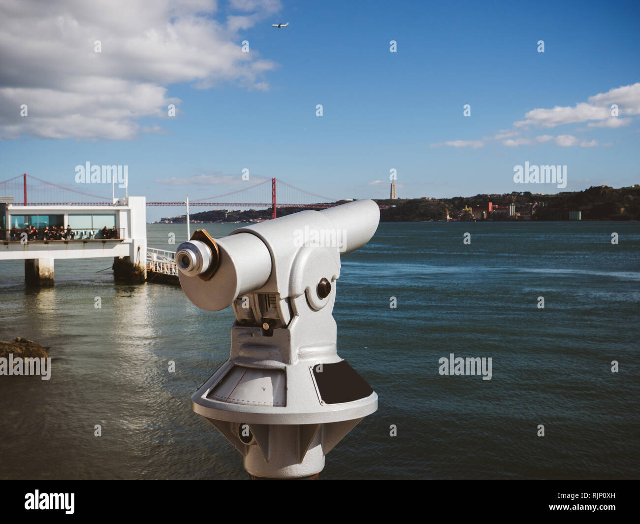 White coin binocular on viewpoint against city river with embankment in sunlight in Lisbon, Portugal - Stock Image