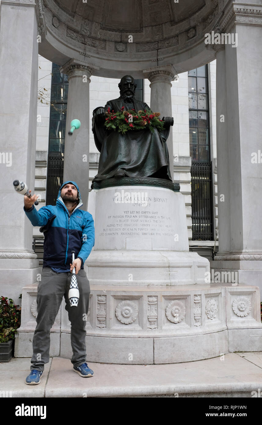 A man practice juggling skills in front of the William Cullen Bryant Memorial in Bryant Park.Midtown Manhattan.New York City.NY.USA - Stock Image