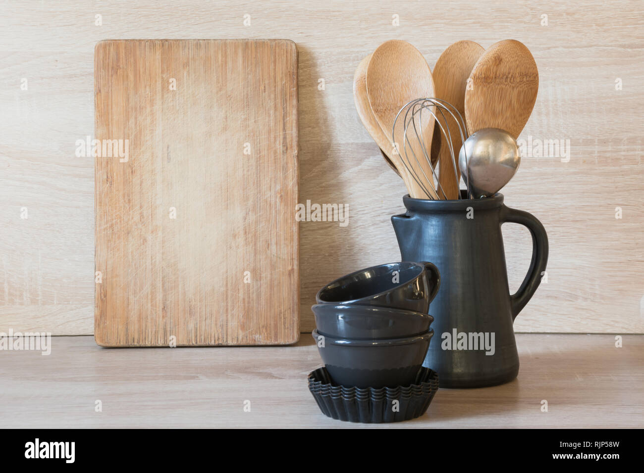 Crockery, clayware utensils and different stuff on wooden tabletop. Kitchen still life as background - Stock Image