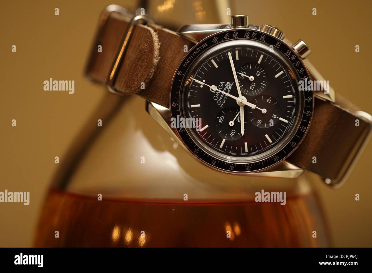 Omega Speedmaster watch on leather nato strap wrapped around bottle of single malt scotch on brown background Stock Photo