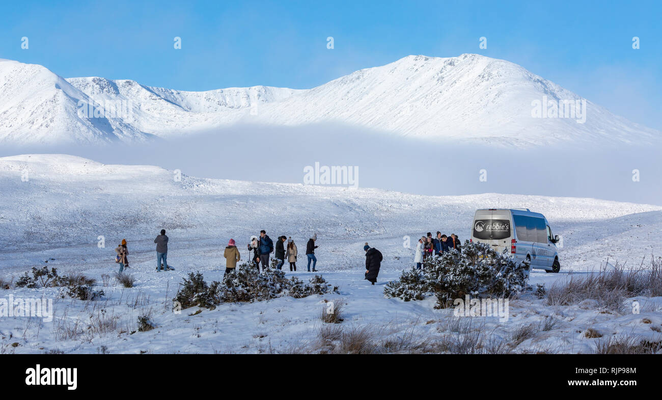 Visitors enjoying the winter scenery on a minibus tour. Loch Tulla viewpoint, A82 road approaching Rannoch Moor, Scotland. - Stock Image