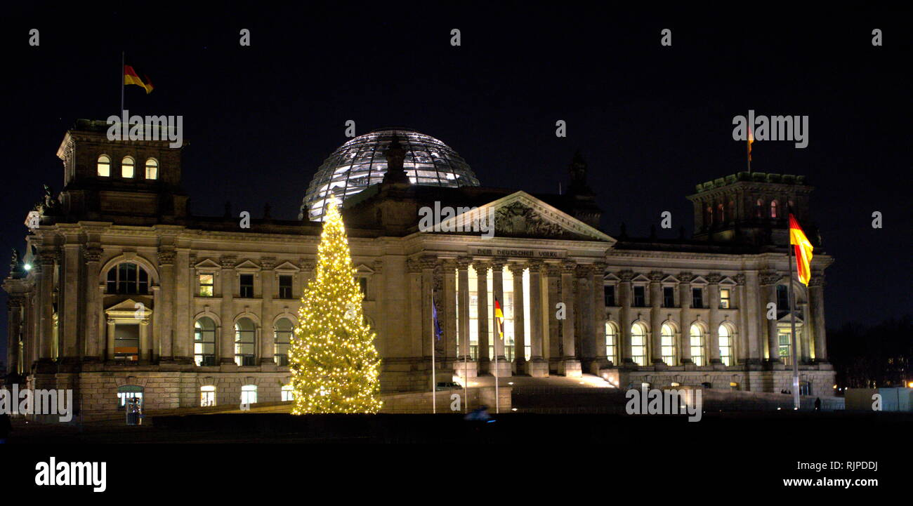 A photograph taken of the exterior of the Reichstag Building, a historic edifice in Berlin, Germany, constructed to house the Imperial Diet of the German Empire. A large Christmas tree illuminates the night sky. - Stock Image